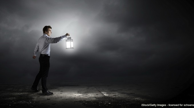 Young handsome businessman walking in darkness with lantern