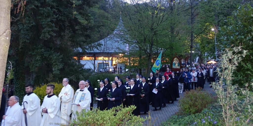 Eine lange Prozession - die Pilger tragen Blumen und Lichter in den Händen. k