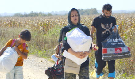 Sid, Serbia - September 18th, 2015: Syrian family walking on the dirt road, preparing to cross the border between Serbia and Croatia, looking for a new life. Mother, father and the son, going to a better future in the EU countries.
