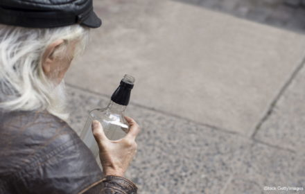 Portrait of a poor senior man sitting on cardboard with a bottle of whiskey. Old drunk man with white beard holding a bottle of whiskey. Close up of homeless sitting on cardboard in a drunken state and drinking whiskey.