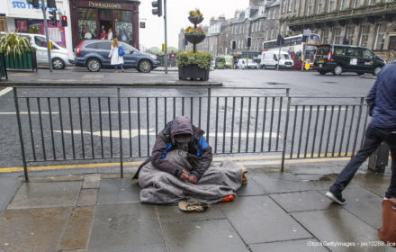 Edinburgh, UK: June 27, 2016: A beggar sits in the rain on a busy junction in Edinburgh. It is raining and he is being ignored by passersby. Begging is illegal under the Vagrancy Act of 1824. However it does not carry a jail sentence and is not well enforced in many cities.