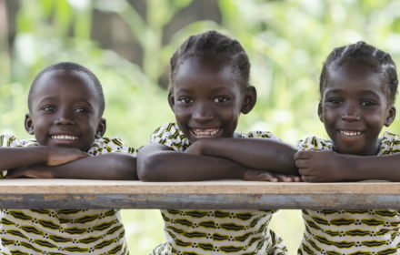 Three African children proudly sitting in their desk at school in Bamako, Mali. Candid outdoor shot of one boy and two girls learning their lessons at school.