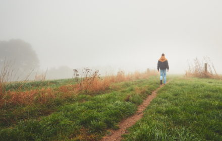 Lonely young man walking in mysterious fog. Autumn morning in beautiful nature in the Czech Republic
