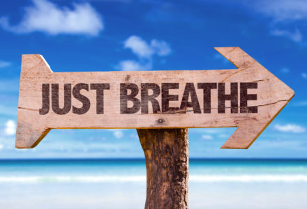 Just Breathe directional sign with a beach