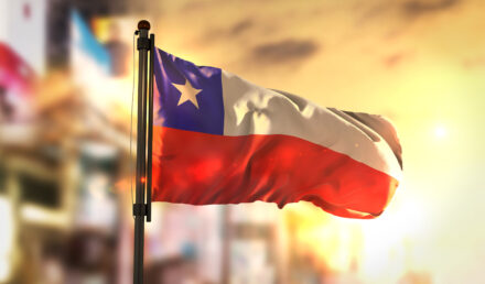 Chile Flag Against City Blurred Background At Sunrise Backlight