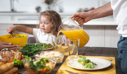 Close up of male hand pouring orange juice into glass. Girl is taking salad from bowl with appetite. Family breakfast concept